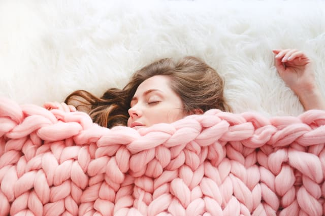 Young woman with long brown hair sleeping under warm knitted peach color throw blanket