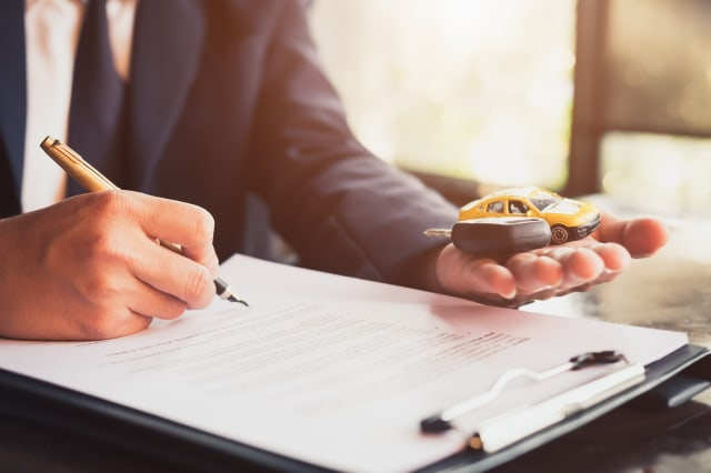 Midsection Of Car Insurance Agent Writing On Form While Holding Key At Office