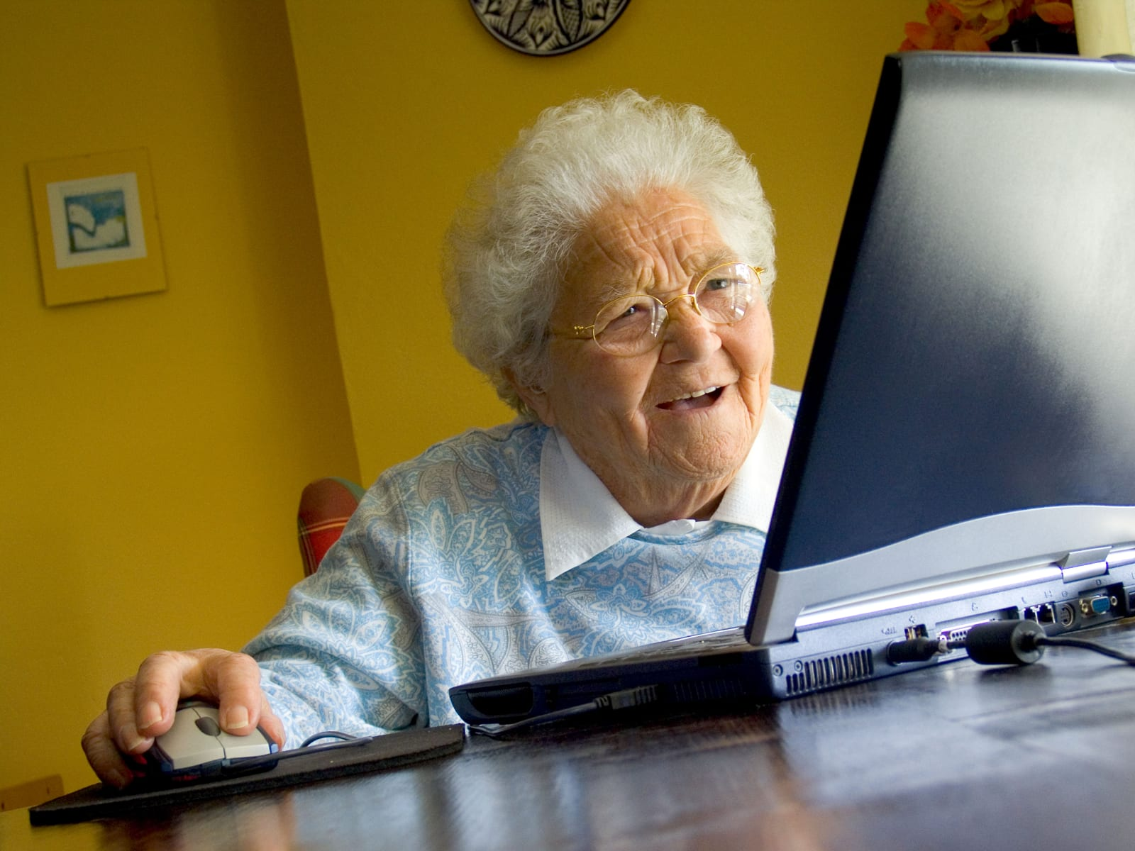 Senior elderly lady at home using her new laptop computer and its technology