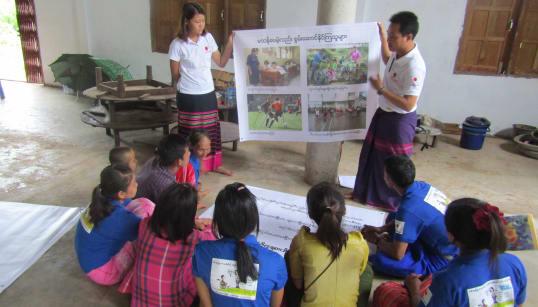 障がい啓発活動の実践について学ぶコミュニティボランティア(手前)。模造紙を手にするのはAAR職員のチョウ・エイ・トゥエ(中央左)とソー・チャウ・エー・カウン(2018年6月13日、カーレー区)