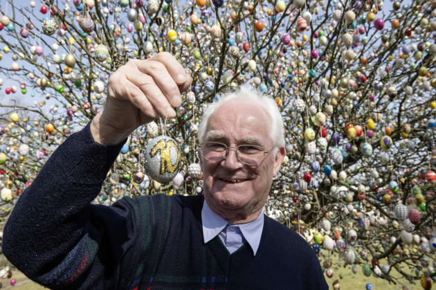 Pensioner Volker Kraft stands next to an apple tree decorated with approximately 10,000 Easter eggs on...