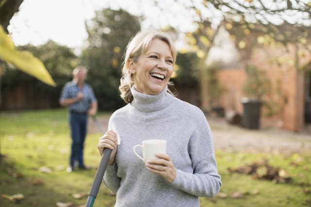 Happy mature woman drinking coffee and raking autumn leaves in backyard
