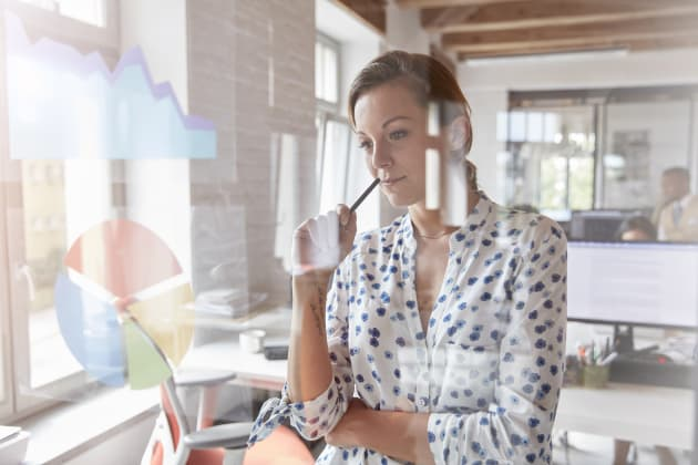 Pensive businesswoman reviewing graph and pie chart on window in office