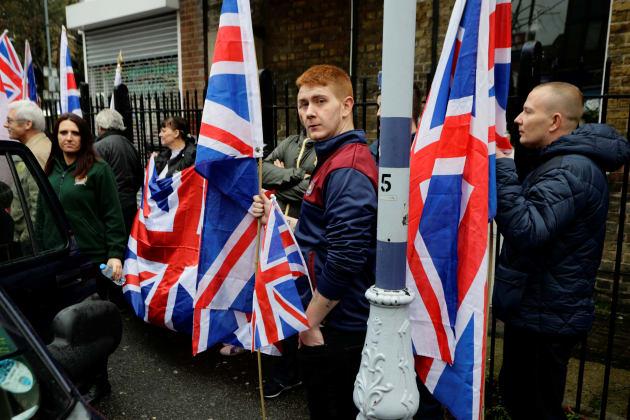 イギリスの国旗を持つブリテン・ファーストの構成員。左側、車の扉の前に立つ女性がジェイダ・フランセン氏。