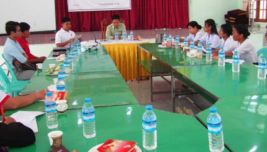 行政職員を前に活動報告を行う当事者コミュニティボランティアのソー・モ・モさん(左から3人目目の白い服を着た男性)(2018年11月、ラインブエ地区)