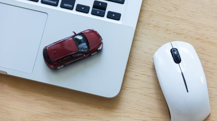 Car model on notebook and mouse on wooden desk