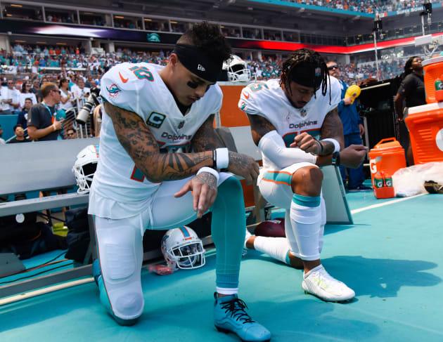 国歌斉唱時、膝をついて起立を拒否するマイアミ・ドルフィンズのケニー・スティルス(左)とアルバート・ウィルソンの2選手=9月9日、フロリダ州