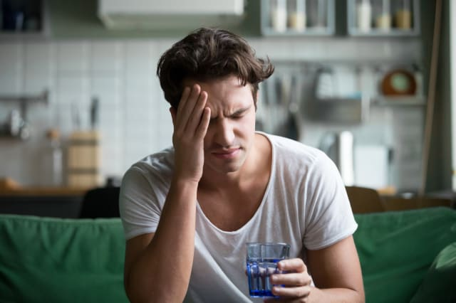 Young man suffering from headache, migraine or hangover at home