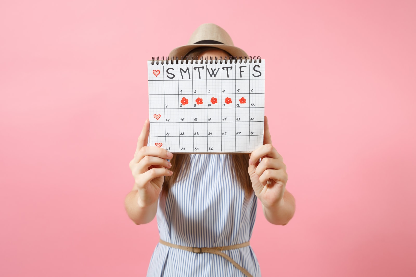 Portrait of woman in blue dress cover face, hiding behind periods calendar for checking menstruation days isolated on trending pink background. Medical, healthcare, gynecological concept. Copy space.
