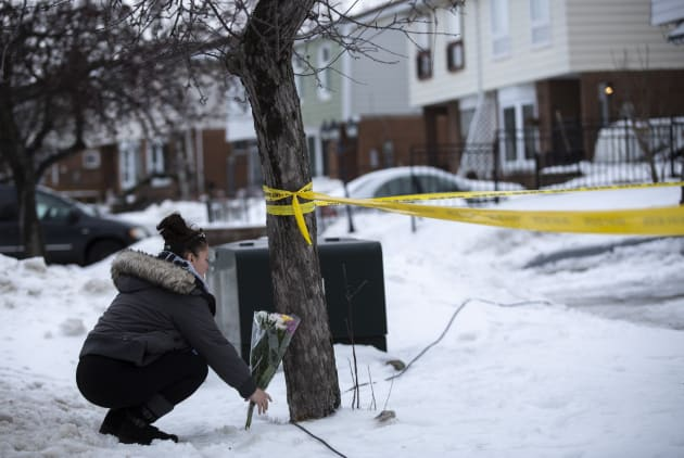 Local resident Jennifer Fuller places flowers at the scene outside of a house where a young girl was found dead in Brampton, Ont. on Feb. 15, 2019.