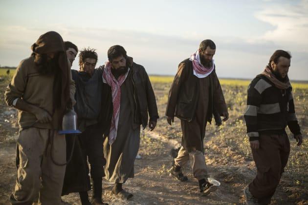 Hombres sospechosos de pertenecer al EI tras rendirse a las fuerzas kurdosirias en la batalla por acabar...