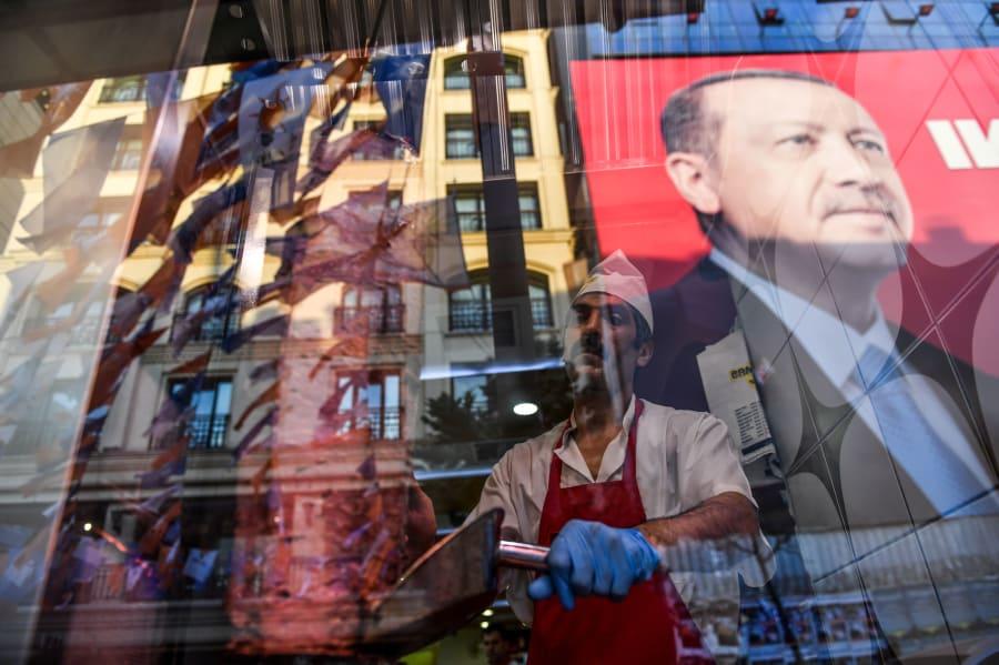 Un poster con el rostro de Recep Tayyip Erdogan se refleja en la vitrina de un restaurante de la plaza Taksim, el 20 de junio de 2018 en Estambul.