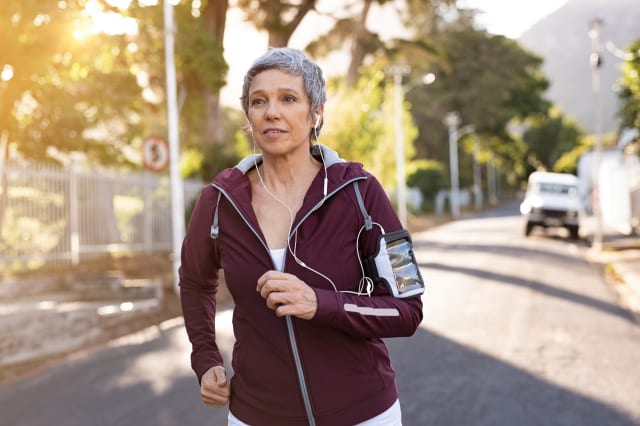 Senior woman jogging in the street