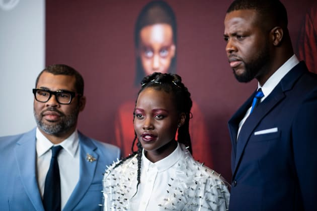 Director/writer Jordan Peele (left) stands next to actress Lupita Nyong'o and actor Winston Duke at the...