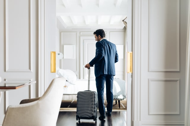 Businessman with wheeled luggage in suite