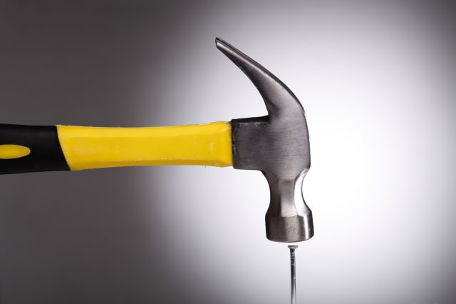 Close-Up Of Nails And Hammer Against Gray Background