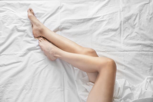 Sexy slender female legs on white bed. Sports and Care Concept