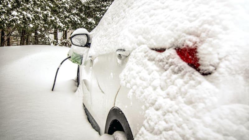 Une voiture électrique en charge après une chute de neige.