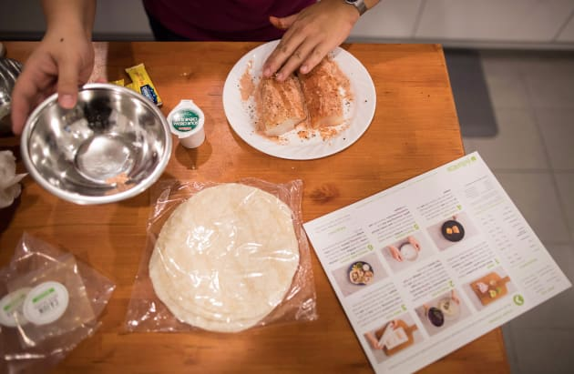 Jayne Zhou seasons fish while preparing cajun fish tacos from a Hello Fresh meal kit at her home in Vancouver...