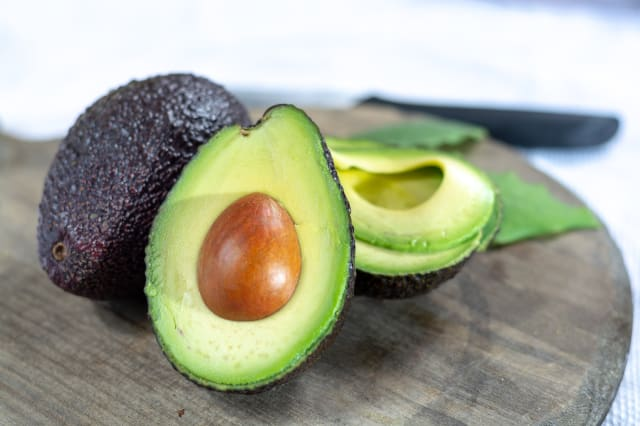 Two ripe raw hass avocados close up