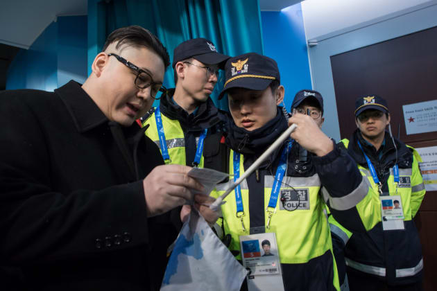 South Korean police check the ticket of a man impersonating North Korean leader Kim Jong Un after he was removed while appearing before North Korean cheerleaders attending the Unified Korean ice hockey game against Japan during the Pyeongchang 2018 Winter Olympic Games at the Kwandong Hockey Centre in Gangneung on February 14, 2018.   / AFP PHOTO / YELIM LEE        (Photo credit should read YELIM LEE/AFP/Getty Images)