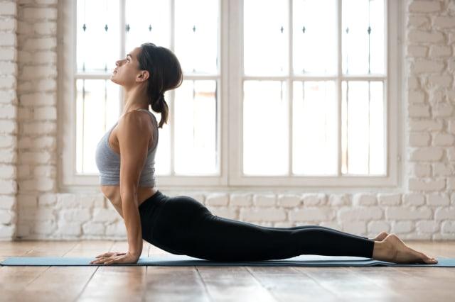 Young sporty woman practicing yoga, doing upward facing dog exercise