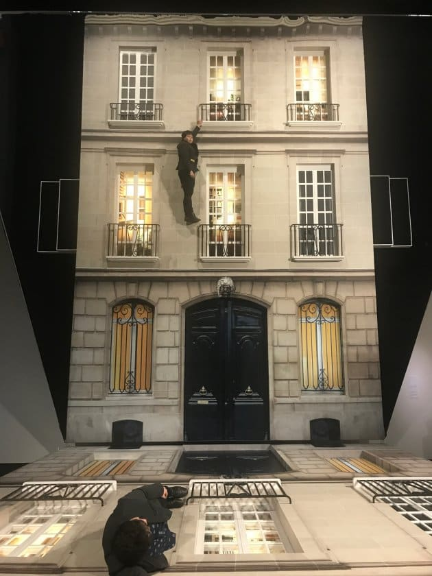 横たわった建物の壁に人々が寝転がり、上部の鏡に映っている自分を眺めているもの。