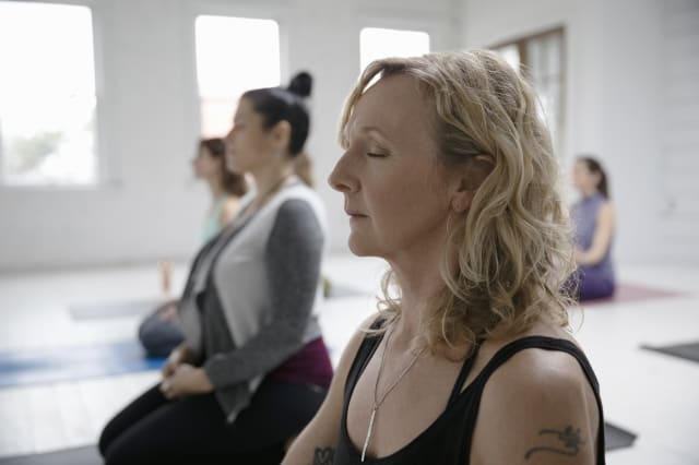 Serene woman meditating in yoga class