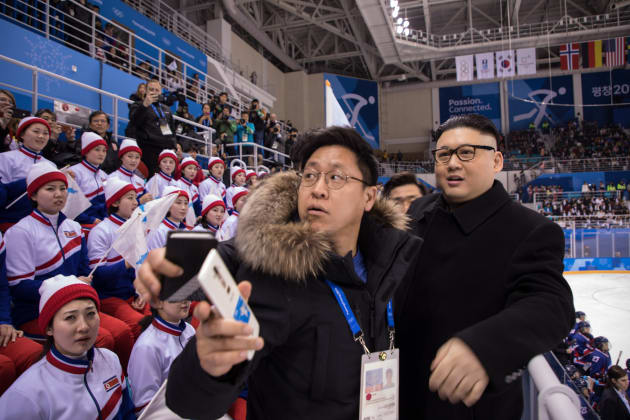 A man impersonating North Korean leader Kim Jong Un is removed by security offices after waving a unified Korean flag before North Korean cheerleaders attending the Unified Korean ice hockey game against Japan during the Pyeongchang 2018 Winter Olympic Games at the Kwandong Hockey Centre in Gangneung on February 14, 2018.   / AFP PHOTO / YELIM LEE        (Photo credit should read YELIM LEE/AFP/Getty Images)