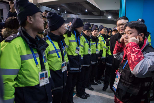 South Korean police surround a man impersonating North Korean leader Kim Jong Un after he appeared before North Korean cheerleaders attending the Unified Korean ice hockey game against Japan during the Pyeongchang 2018 Winter Olympic Games at the Kwandong Hockey Centre in Gangneung on February 14, 2018.   / AFP PHOTO / YELIM LEE        (Photo credit should read YELIM LEE/AFP/Getty Images)