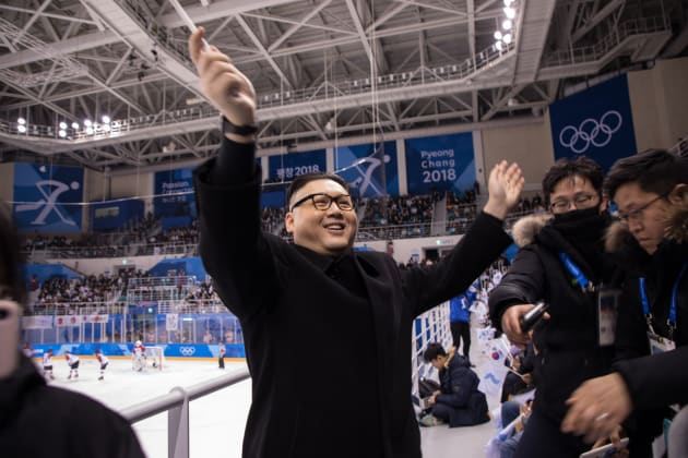 A man impersonating North Korean leader Kim Jong Un waves a unified Korean flag before North Korean cheerleaders attending the Unified Korean ice hockey game against Japan during the Pyeongchang 2018 Winter Olympic Games at the Kwandong Hockey Centre in Gangneung on February 14, 2018.   / AFP PHOTO / YELIM LEE        (Photo credit should read YELIM LEE/AFP/Getty Images)