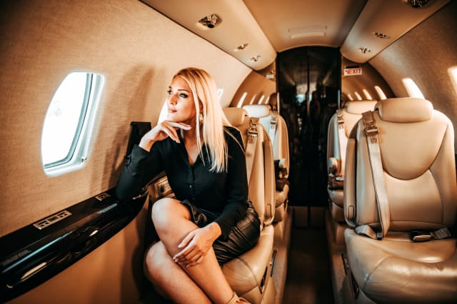 Rich blond woman looking through window and thinking while traveling aboard a private airplane