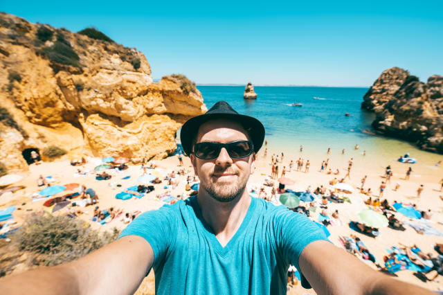 Man takes selfie on crowded beach, Portugal