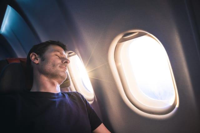 Man sleeping on airplane during sunrise