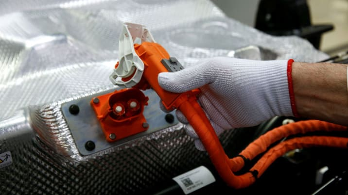 FILE PHOTO: Worker connects the battery during the assembly of a VW e-Golf electric car at the Transparent Factory in Dresden