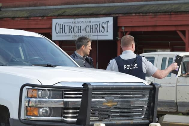 RCMP officers talk behind a barricade in front of the Church of Christ in Salmon Arm, B.C. on April 14,