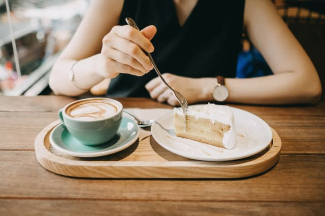 Woman having a relax time eating a slice of cake and having coffee in cafe