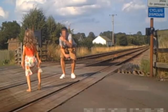 Shocking CCTV footage has been released which shows people risking their lives on level crossings - including a father and his young daughter posing for a photo shoot.