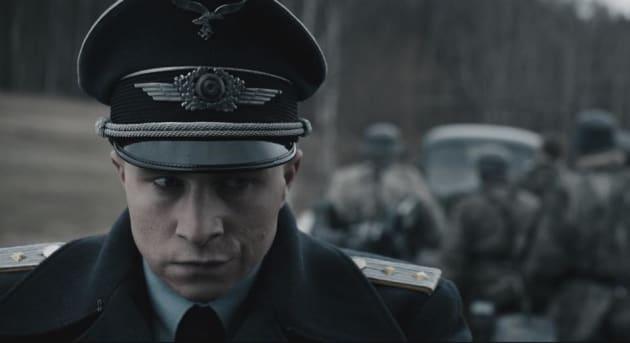 軍服に身を包み不敵な笑みを浮かべるマックス・フーバッヒャー