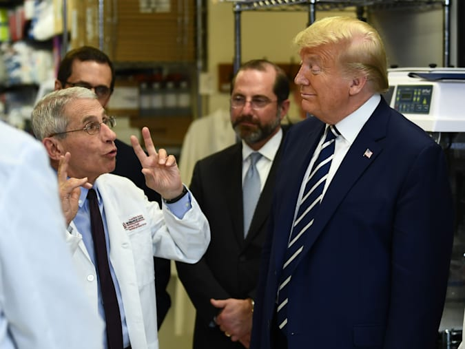 """National Institute of Allergy and Infectious Diseases Director Tony Fauci speaks to US President Donald Trump during a tour of the National Institutes of Health's Vaccine Research Center March 3, 2020, in Bethesda, Maryland. - The US Federal Reserve announced an emergency rate cut responding to the growing economic risk posed by the coronavirus epidemic after the UN health agency said the world has entered """"uncharted territory"""" with the outbreak's rapid spread. (Photo by Brendan Smialowski / AFP) (Photo by BRENDAN SMIALOWSKI/AFP via Getty Images)"""
