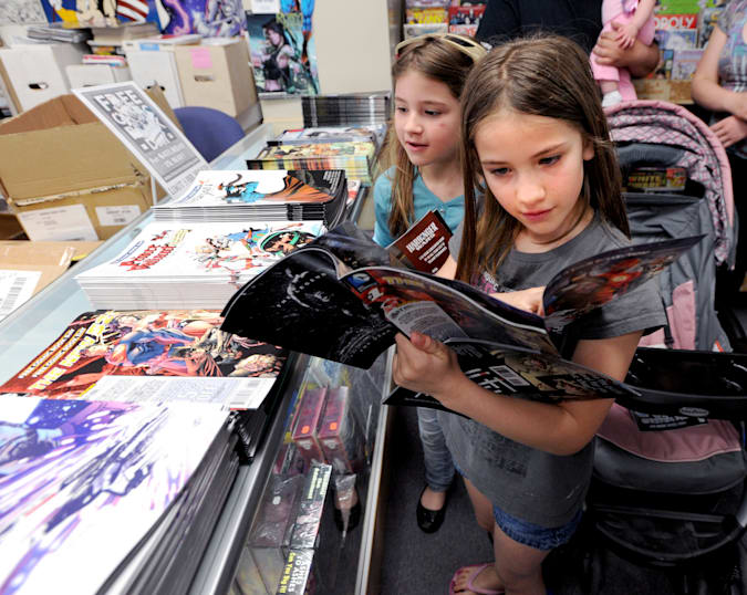 Nikki Beck, 9, right, and her sister, Alana, 8, both of Firestone, look through the free comics in order to make their choice.Time Warp Comics in Boulder is one of thousands of comic book shops around the world celebrating Free Comic Book Day on May 4th. On Free Comic Book Day, over 3.3 million comic books will be given away by participating stores.(Photo by Cliff Grassmick/Digital First Media/Boulder Daily Camera via Getty Images)