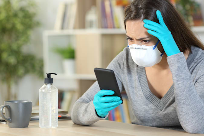 Worried girl with latex gloves and protective mask reads covid-19 news on smart phone sitting at home