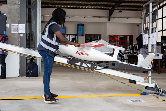 """A staff member prepares a drone for the delivery of medical supplies at the drone delivery service base run by operator Zipline in Omenako, 70 kilometres (40 miles) north of Accra on April 23, 2019. - Ghana launched a fleet of drones on April 24, 2019 to carry medical supplies to remote areas, with Ghana's President declaring it would become the """"world's largest drone delivery service."""" The craft are part of an ambitious plan to leapfrog problems of medical access in a country with poor roads. The drones have been flying test runs with blood and vaccines, but the project was officially inaugurated Wednesday at the main drone base in Omenako, 70 kilometres (40 miles) north of Accra. Operator Zipline, a US-based company, said the three other sites should be up and running by the end of 2019. The drones are planned to ferry 150 different medicines, blood, and vaccines to more than 2,000 clinics serving over 12 million people -- roughly 40 percent of the population. (Photo by Ruth McDowall / AFP)        (Photo credit should read RUTH MCDOWALL/AFP via Getty Images)"""