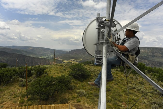 MEEKER, CO - AUGUST: Jackson Federico, a tower technician for Advanced Wireless Solutions, works to make some repairs on the dish on the Pollard cell tower high off the ground in rural Rio Blanco County  on July 12, 2017 near Meeker, Colorado.  Broadband in Rio Blanco county and Meeker is some of the best in the state for rural areas. (Photo by Helen H. Richardson/MediaNews Group/The Denver Post via Getty Images)