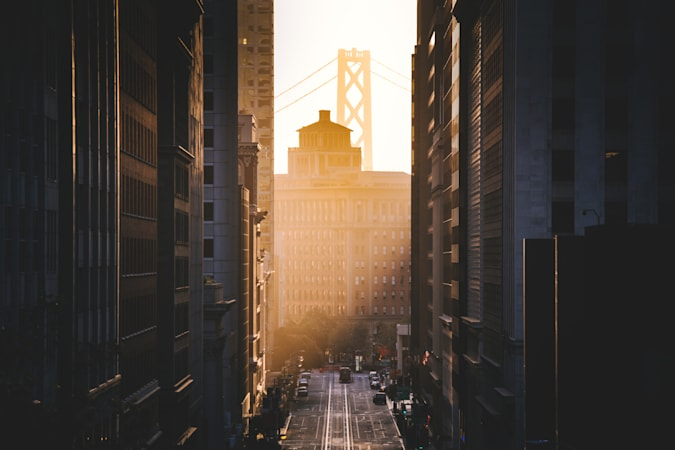Classic view of historic California Street with famous Oakland Bay Bridge illuminated in first golden morning light at sunrise in summer, San Francisco, California, USA