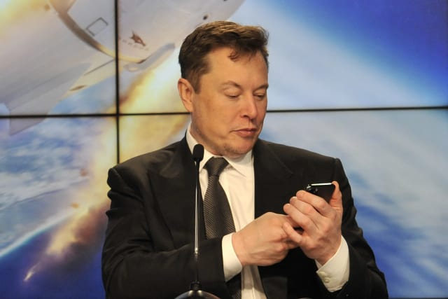 SpaceX founder and chief engineer Elon Musk looks at his mobile phone during a post-launch news conference to discuss the SpaceX Crew Dragon astronaut capsule in-flight abort test at the Kennedy Space Center in Cape Canaveral, Florida, U.S. January 19, 2020. REUTERS/Steve Nesius
