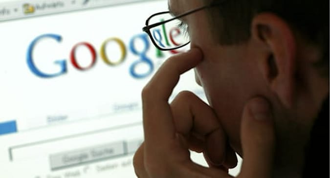 Man in front of a display with the website of the internet search engine Google.