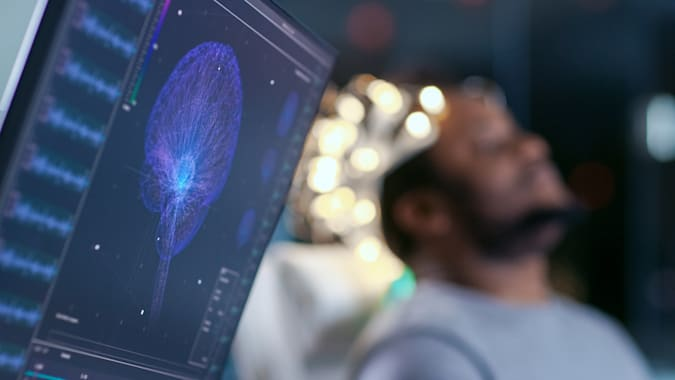 Los monitores muestran la lectura de EEG y el modelo gráfico del cerebro. En el laboratorio de fondo, el hombre con auriculares de exploración de ondas cerebrales se sienta en una silla con los ojos cerrados. En el Laboratorio de Investigación del Estudio del Cerebro Moderno