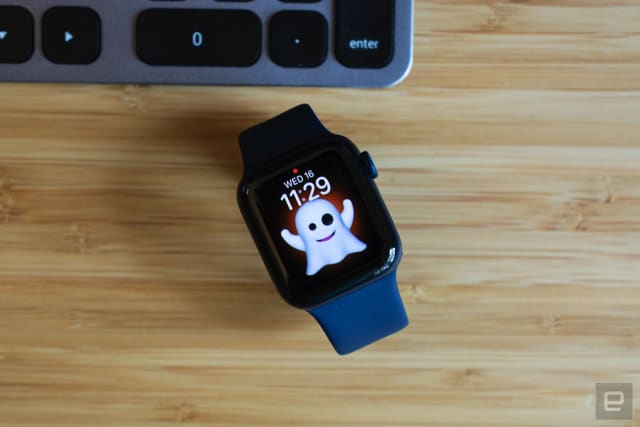 The Apple Watch Series 6 with a Memoji watch face sitting on a wooden table.
