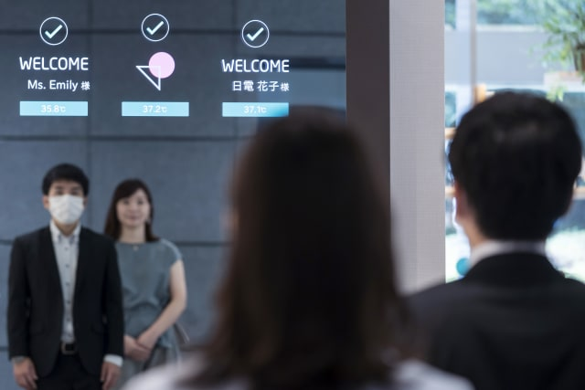"TOKYO, JAPAN - JULY 13: Employees stand in front of a monitor during a demonstration of the smart gateless and touchless entrance that allows temperature checks and face recognition for masked faces at the NEC Corporation headquarters on July 13, 2020 in Tokyo, Japan. NEC Corporation has transformed its Tokyo headquarters skyscraper into a smart building to showcase its ""new normal"" technologies and services to facilitate worker safety and organizational efficiency for the post COVID-19 world. (Photo by Tomohiro Ohsumi/Getty Images for NEC Corporation)"